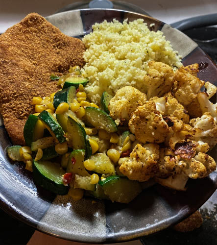 Pork Chops with zucchini, corn, buffalo roasted cauliflower, and cous cous.